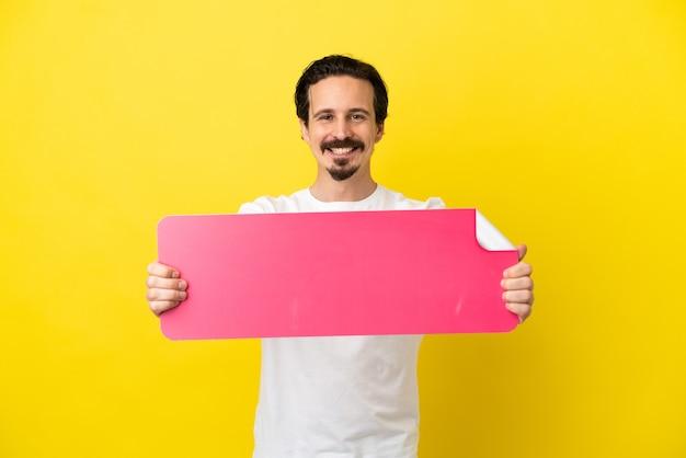 Jovem homem caucasiano isolado em um fundo amarelo segurando um cartaz vazio