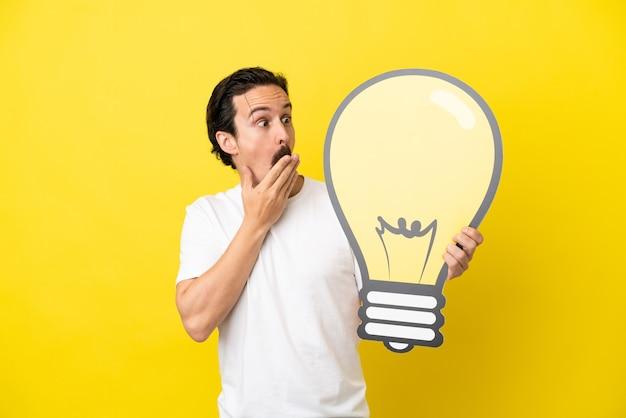 Jovem homem caucasiano isolado em um fundo amarelo segurando um ícone de lâmpada com expressão de surpresa