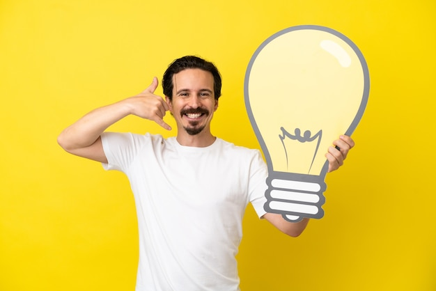 Jovem homem caucasiano isolado em um fundo amarelo segurando um ícone de lâmpada e fazendo gestos de telefone