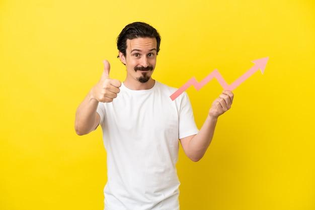 Jovem homem caucasiano isolado em um fundo amarelo segurando uma flecha ascendente com o polegar para cima