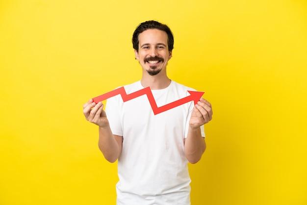 Jovem homem caucasiano isolado em um fundo amarelo segurando uma flecha ascendente com uma expressão feliz