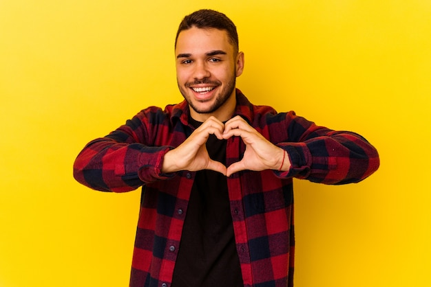 Jovem homem caucasiano isolado em um fundo amarelo, sorrindo e mostrando uma forma de coração com as mãos.