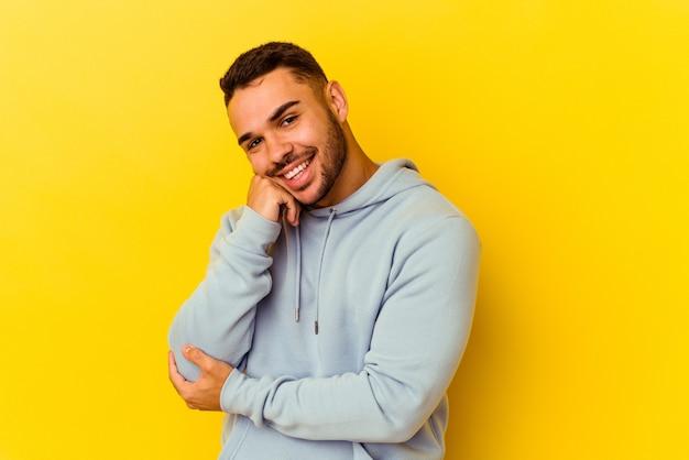 Jovem homem caucasiano isolado em um fundo amarelo, sorrindo feliz e confiante, tocando o queixo com a mão.