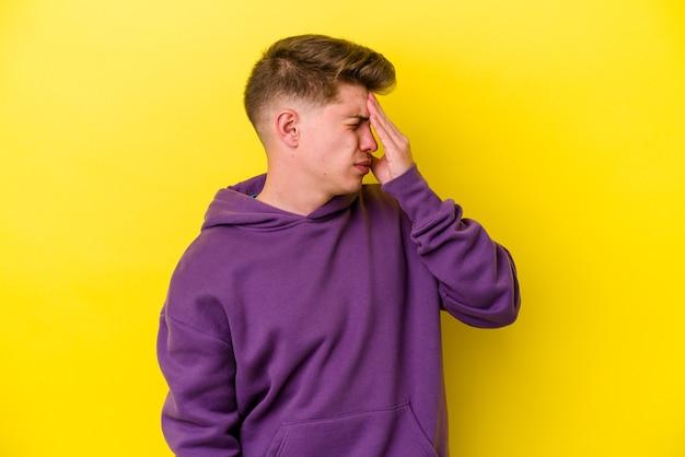 Jovem homem caucasiano isolado em um fundo amarelo, tendo uma dor de cabeça, tocando a frente do rosto.