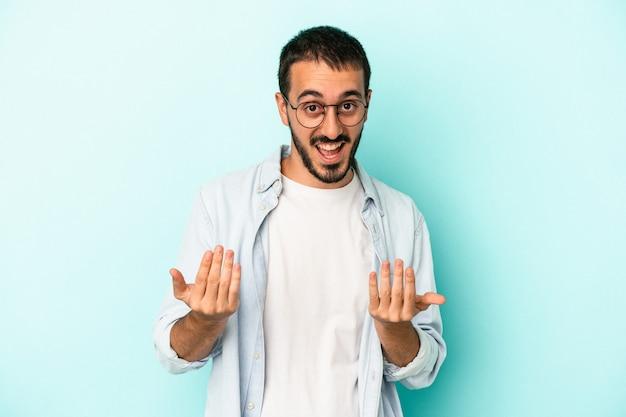 Jovem homem caucasiano isolado em um fundo azul, apontando com o dedo para você, como se fosse um convite para se aproximar.