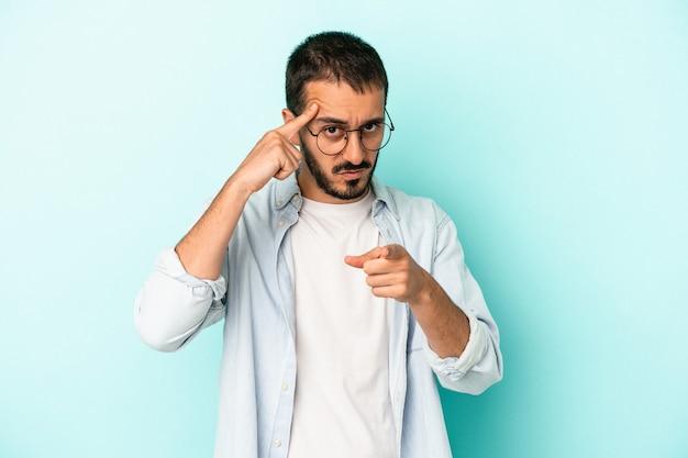 Jovem homem caucasiano isolado em um fundo azul, apontando o templo com o dedo, pensando, focado em uma tarefa.