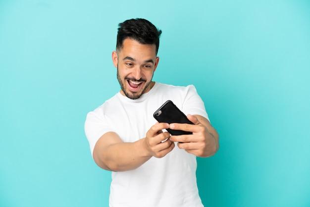 Jovem homem caucasiano isolado em um fundo azul brincando com o celular