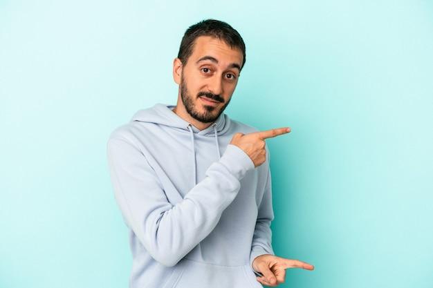 Jovem homem caucasiano isolado em um fundo azul chocado apontando com o dedo indicador para um espaço de cópia.