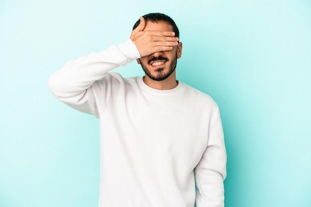 Jovem homem caucasiano isolado em um fundo azul cobre os olhos com as mãos, sorri à espera de uma surpresa.