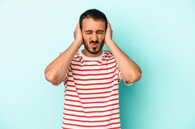 Jovem homem caucasiano isolado em um fundo azul, cobrindo as orelhas com as mãos.