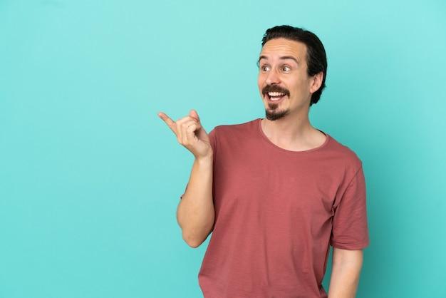 Jovem homem caucasiano isolado em um fundo azul com a intenção de descobrir a solução enquanto levanta um dedo