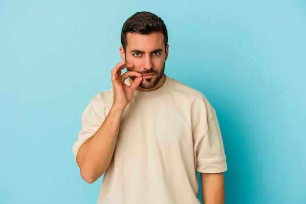Jovem homem caucasiano isolado em um fundo azul com os dedos nos lábios, mantendo um segredo.