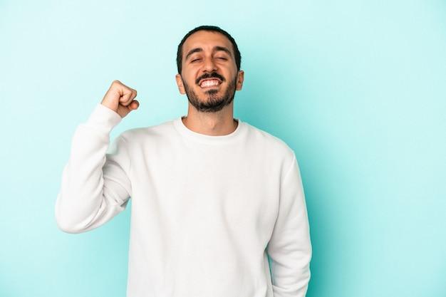 Jovem homem caucasiano isolado em um fundo azul, comemorando uma vitória, paixão e entusiasmo, expressão feliz.