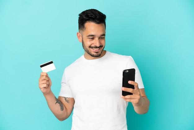 Jovem homem caucasiano isolado em um fundo azul comprando com o celular com um cartão de crédito