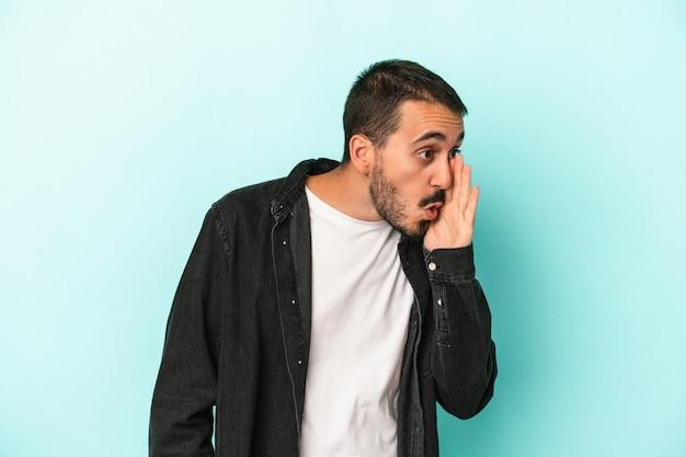 Jovem homem caucasiano isolado em um fundo azul contando uma notícia secreta sobre a travagem e olhando para o lado