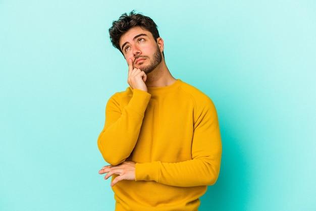Jovem homem caucasiano isolado em um fundo azul, contemplando, planejando uma estratégia, pensando na forma de um negócio.