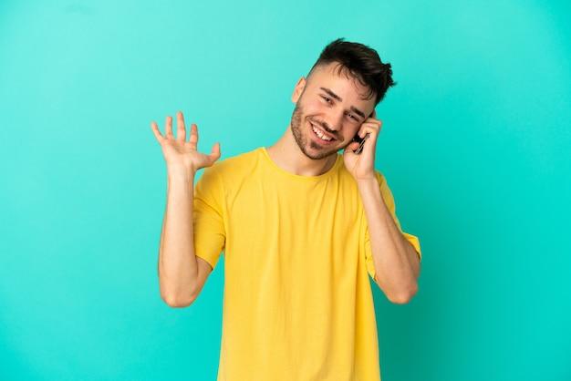 Jovem homem caucasiano isolado em um fundo azul, conversando com alguém ao telefone celular