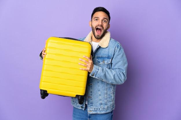 Jovem homem caucasiano isolado em um fundo azul de férias com mala de viagem e surpreso
