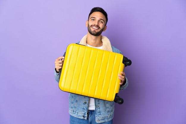 Jovem homem caucasiano isolado em um fundo azul de férias com mala de viagem.