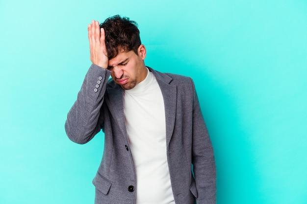 Jovem homem caucasiano isolado em um fundo azul, esquecendo de algo, batendo na testa com a palma da mão e fechando os olhos.