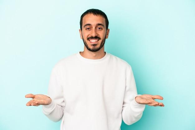 Jovem homem caucasiano isolado em um fundo azul faz escala com os braços, sente-se feliz e confiante.
