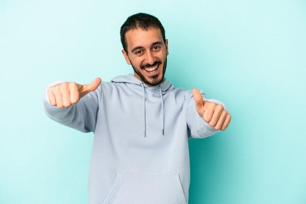 Jovem homem caucasiano isolado em um fundo azul, levantando os dois polegares, sorrindo e confiante.