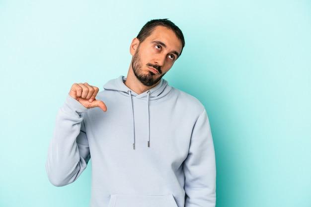 Jovem homem caucasiano isolado em um fundo azul, mostrando um gesto de antipatia, polegares para baixo. conceito de desacordo.