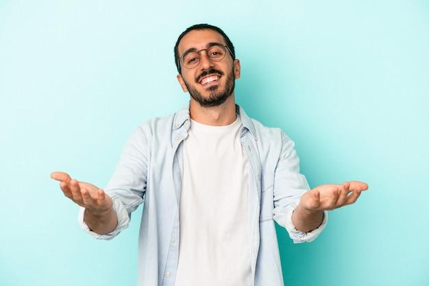 Jovem homem caucasiano isolado em um fundo azul, mostrando uma expressão de boas-vindas.
