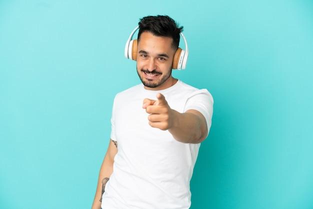 Jovem homem caucasiano isolado em um fundo azul ouvindo música e apontando para a frente