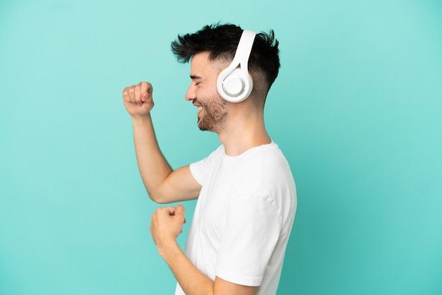 Jovem homem caucasiano isolado em um fundo azul ouvindo música e dançando