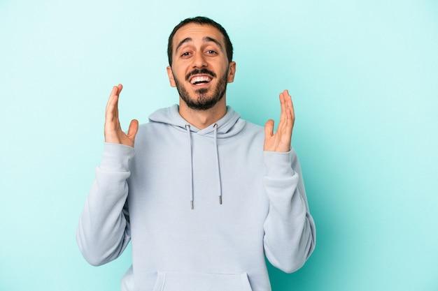Jovem homem caucasiano isolado em um fundo azul ri alto, mantendo a mão no peito.