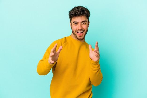 Jovem homem caucasiano isolado em um fundo azul se sente confiante dando um abraço para a câmera.
