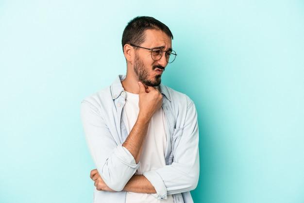 Jovem homem caucasiano isolado em um fundo azul sofre de dor na garganta devido a um vírus ou infecção.