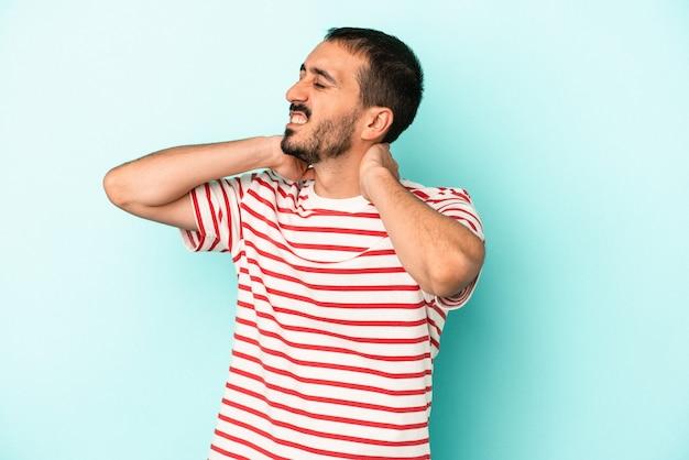 Jovem homem caucasiano isolado em um fundo azul, sofrendo de dores no pescoço devido ao estilo de vida sedentário.