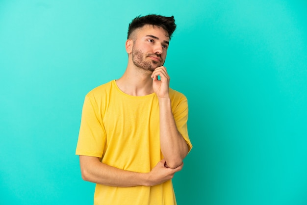 Jovem homem caucasiano isolado em um fundo azul, tendo dúvidas e pensando