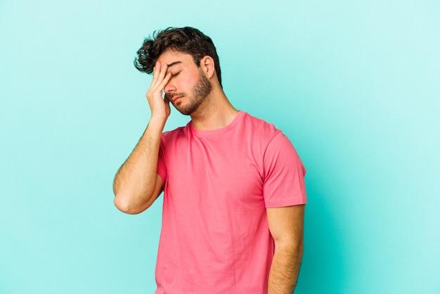 Jovem homem caucasiano isolado em um fundo azul, tendo uma dor de cabeça, tocando a frente do rosto.