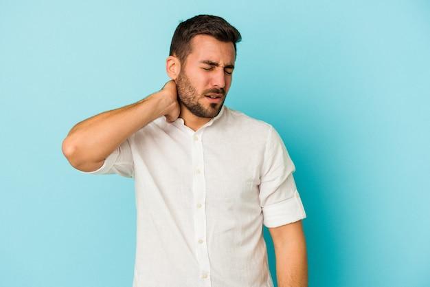 Jovem homem caucasiano isolado em um fundo azul, tendo uma dor no pescoço devido ao estresse, massageando e tocando com a mão.
