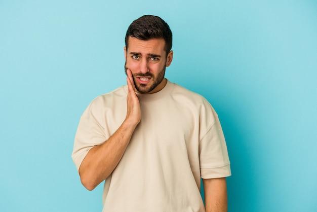 Jovem homem caucasiano isolado em um fundo azul, tendo uma forte dor nos dentes, dor molar.