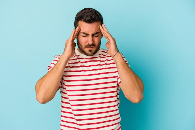 Jovem homem caucasiano isolado em um fundo azul, tocando as têmporas e tendo dor de cabeça.