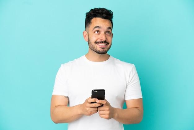 Jovem homem caucasiano isolado em um fundo azul usando telefone celular e olhando para cima