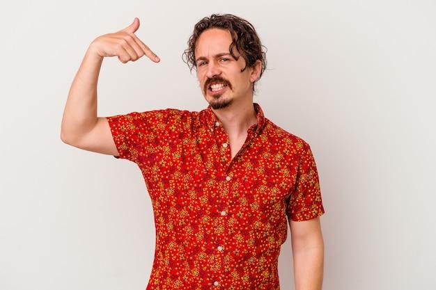 Jovem homem caucasiano isolado em um fundo branco pessoa apontando com a mão para um espaço de cópia de camisa, orgulhoso e confiante