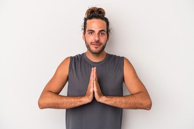 Jovem homem caucasiano isolado em um fundo cinza orando, mostrando devoção, pessoa religiosa em busca de inspiração divina.