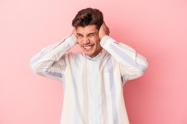 Jovem homem caucasiano isolado em um fundo rosa, cobrindo as orelhas com as mãos.