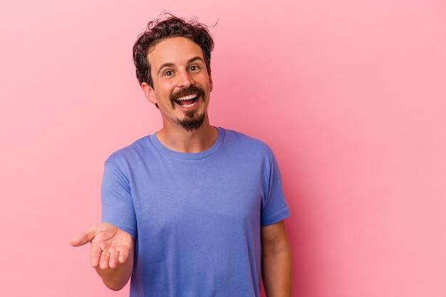 Jovem homem caucasiano isolado em um fundo rosa, esticando a mão para a câmera em um gesto de saudação.