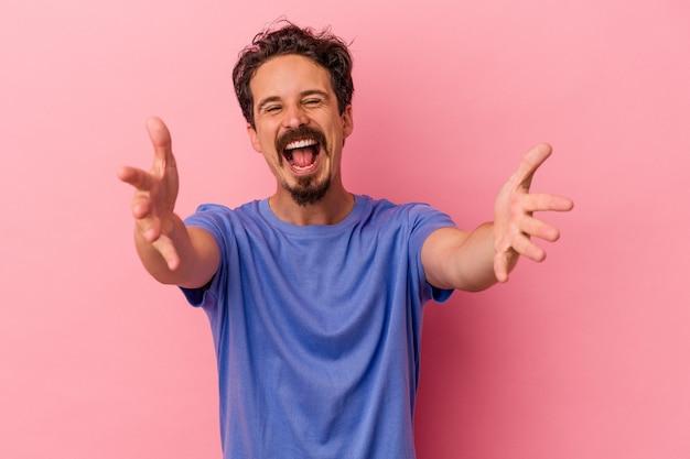 Jovem homem caucasiano isolado em um fundo rosa se sente confiante dando um abraço para a câmera.