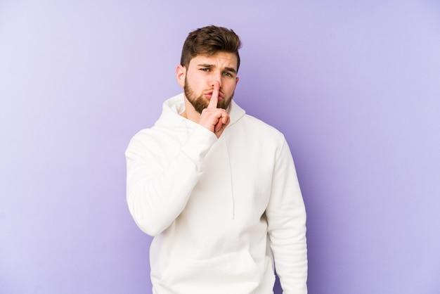Jovem homem caucasiano isolado em um fundo roxo, mantendo um segredo ou pedindo silêncio.