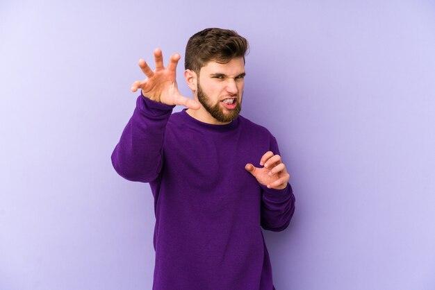 Jovem homem caucasiano isolado em um fundo roxo, mostrando garras imitando um gato, gesto agressivo.