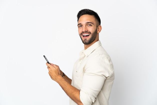 Jovem homem caucasiano isolado em uma parede branca enviando uma mensagem ou e-mail com o celular