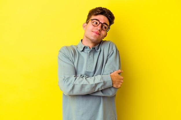 Jovem homem caucasiano isolado na parede amarela abraços, sorrindo despreocupado e feliz.