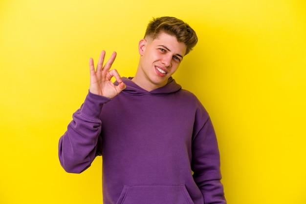 Jovem homem caucasiano isolado na parede amarela pisca um olho e segura um gesto de ok com a mão.